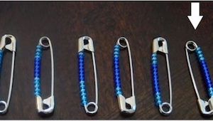 Žena vkládá 12 korálků na zapínací špendlík , pak bere gumičku a vytváří něco úž