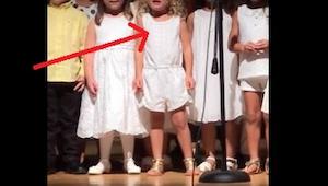 Pozorně sledujte holčičku stojící uprostřed. Když začnou školkaři zpívat, svým v