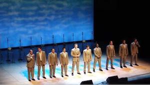 Skupina mužů přichází na scénu. Za okamžik nemá konce smích a pískání publika.