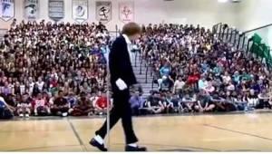 Náctiletý kluk vchází do tělocvičny a jakmile začne hrát hudba, celý dav při poh